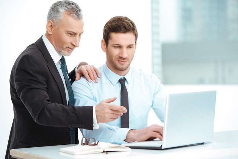 Portrait of aged and young businessmen in office with big window. Businessmen having meeting and transfering knowledge