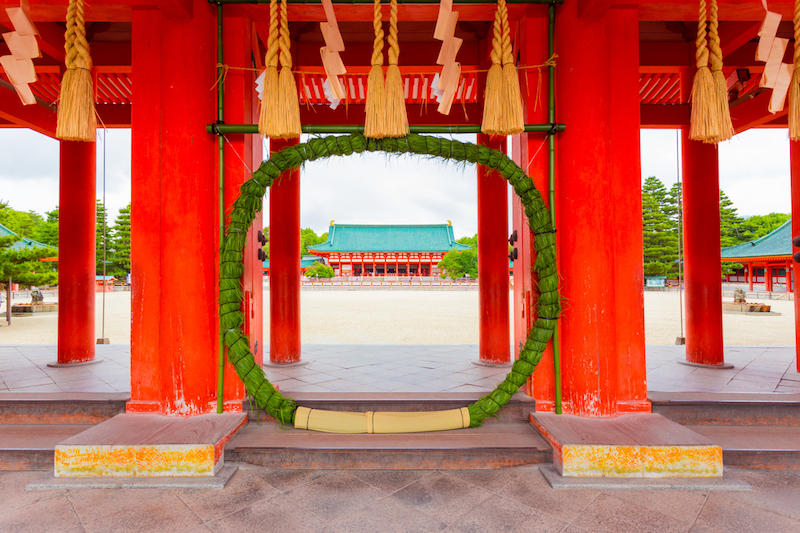Kyoto, Japan - June 19, 2015: Green chinowa kuguri, a circular grass wreath for purification at entrance tower door into Heian-Jingu Shrine open to the inner courtyard and Taikyokuden main building in Kyoto, Japan. Horizontal