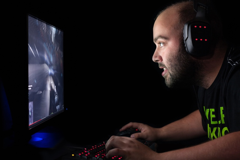 Gamer playing first person shooter game on high end pc