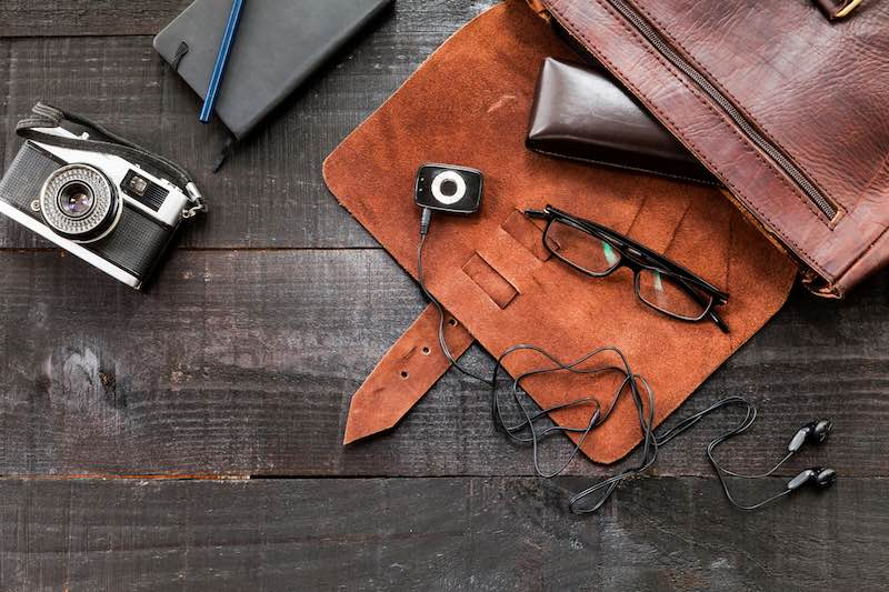The image shows a retro or hipster bag for man or woman with stuff such as glasses , vintage camera, leather bag and a book note