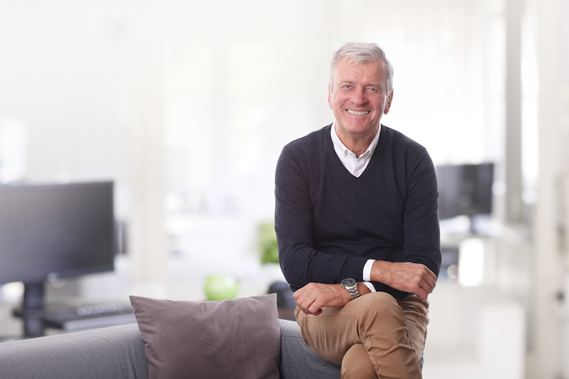 Portrait of confident senior director sitting at his office while looking at camera and smiling.
