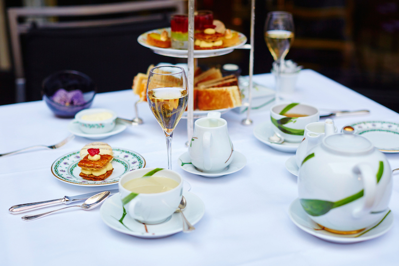 Beautiful table setting with selection of sandwiches, fancy cakes, tea and champagne served for the ceremony of afternoon tea