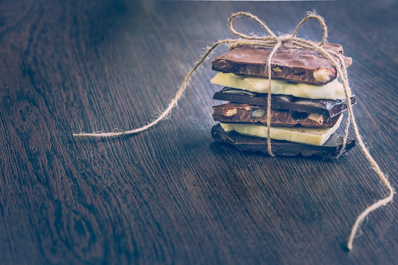 A tower of chocolate bars wrapped like a chocolate present . Various chocolate pieces over dark wood background.