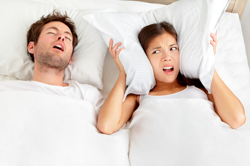 """""""Snoring man. Couple in bed, man snoring and xwoman can not sleep, covering ears with pillow for snore noise. Young interracial couple, Asian woman, Caucasian man sleeping in bed at home. Click on the banners for more of the same:"""""""