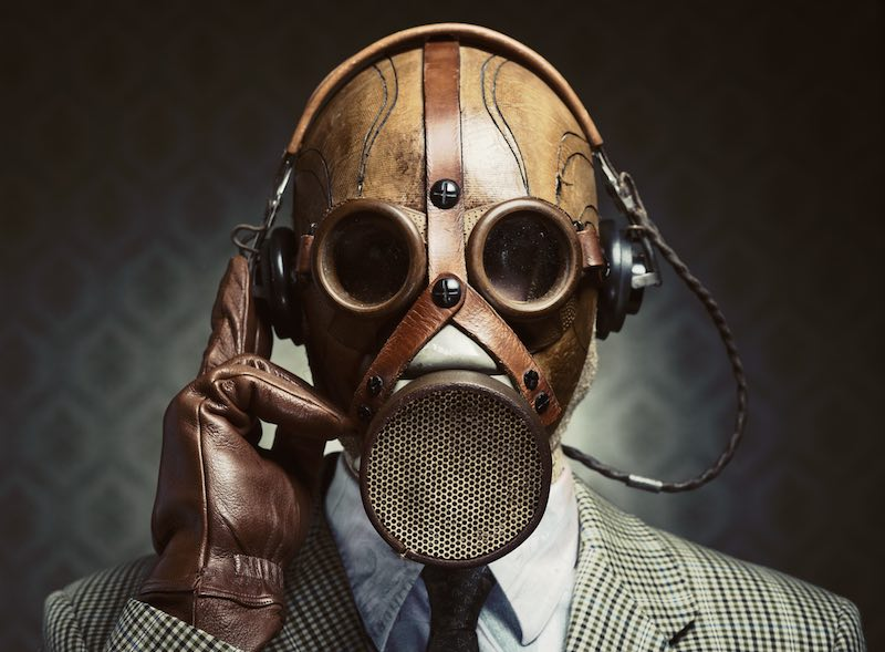 Man wearing vintage gas mask and headphones listening to music.