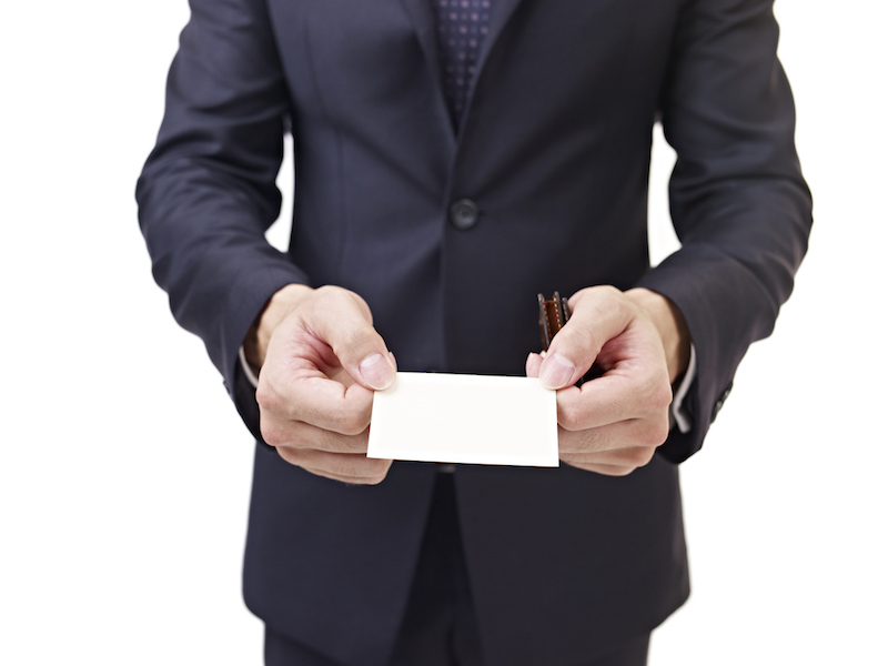 businessman holding business card, isolated on white.