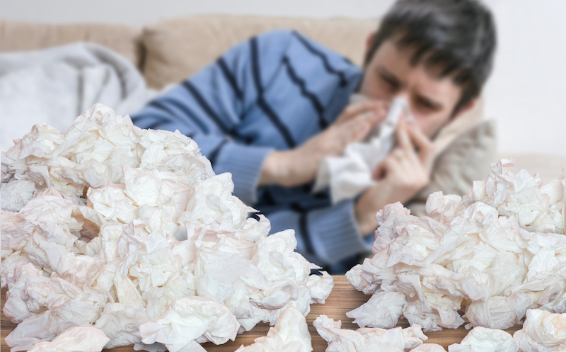 Funny sick man who has flu or cold is blowing his nose. Pile of tissues in front.