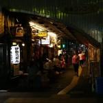 Tokyo, Japan - May 16, 2015: People drinking and eating at old fashion small Izakaya(Japanese bars) under the Train tracks in Yurakucho Tokyo,Japan. Many of those style bars around this area.